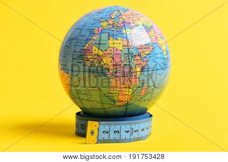 Africa on geographical globe which stands on measuring tape roll on bright yellow background. Symbol of travel and geography