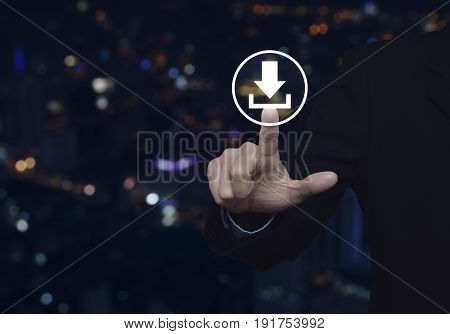 Businessman pressing download icon over blur colorful night light city tower Business internet concept