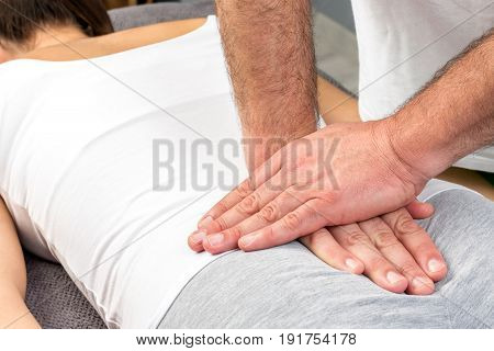 Close up of hands applying physical pressure on female tailbone.