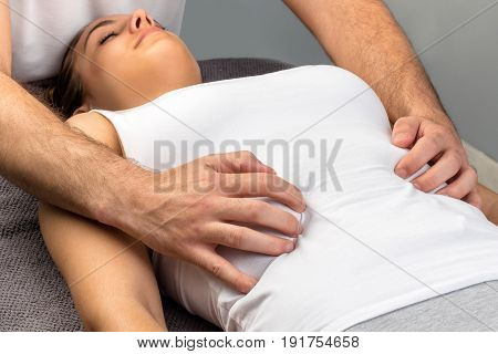 Close up of hands doing physical osteopathic thorax massage on young woman.