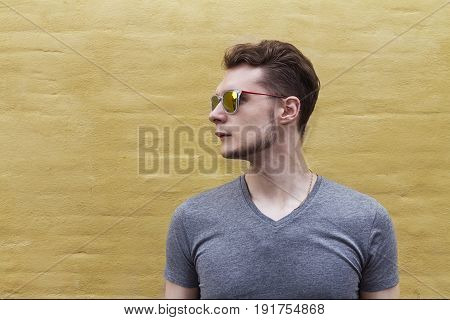 Pretty handsome confident young man hipster with sunglasses smiling behind yellow wall. Looking aside. Horizontal.
