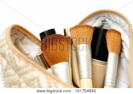 Open cosmetic bag with makeup brushes and cosmetics. Isolated on white