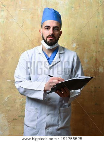 Surgeon With Beard And Tired Face Expression Writes In Notebook