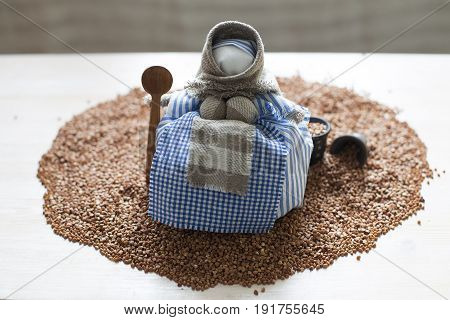 Handmade traditional textile doll with spoon on a heap of buckwheat. Close up