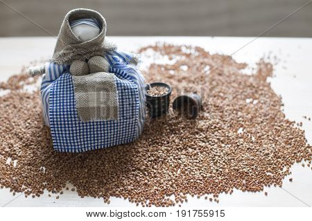 Heap of buckwheat with a traditional textile doll on it. Close up