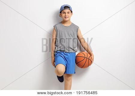 Boy with a basketball leaning against a wall