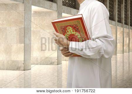 Muslim Man Holding The Holy Book Koran