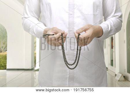 Muslim Man Raising Hand And Praying With Prayer Beads