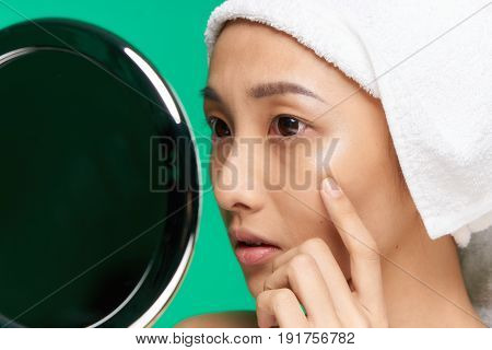 Woman looking in the mirror, woman with a towel on her head, woman on a green background portrait.