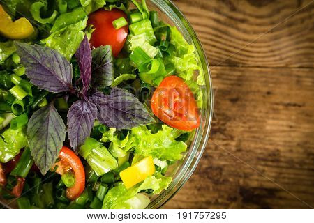 Plenty of cut vegetables on glass bowl on rustic wooden table, empty space for text, closeup