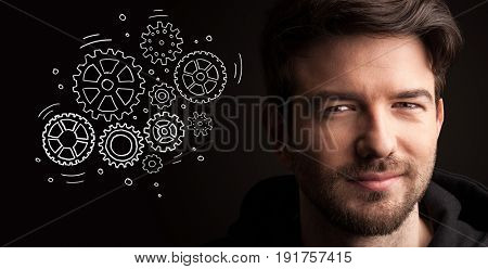 Portrait of a young businessman with rotating gears next to him on a dark background