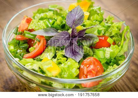 Plenty of cut vegetables on glass bowl on rustic wooden table, closeup