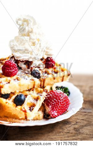 Traditional Belgian waffles with ice cream and fruits on wooden board isolated