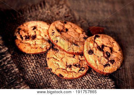 Chocolate cookies on dark napkin on wooden table. Chocolate chip cookies on brown coffee color cloth macro top view