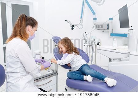 Adorable little girl sitting on chair in dentist cabinet with medic preparing for making a treatment procedure. Dentist and child in cabinet. Dentist office. Little girl sitting in the dentists office
