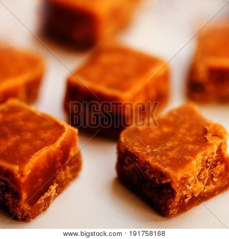 Toffees. Caramel pieces with copy space for your design over dark wooden background close up image.