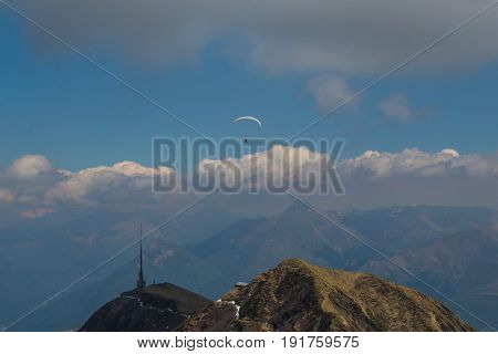 One paraglider in the mountains with blue sky and clouds with sunshine