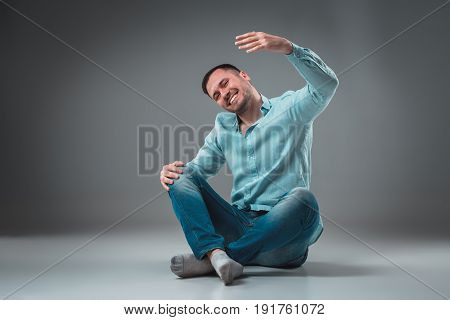 Handsome young man sitting on a floor with raised hands, isolated on gray background. Emotion concept