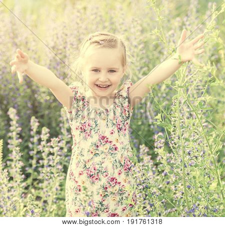 Adorable child in the field among flowers and herbs happy and raising her arms, smiling