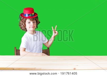 Little Curly Boy In A White Shirt And A Crimson Hat Clown Shows Gesture