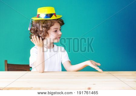 Little Curly Boy In Yellow Hat Clown Threw Up His Hands, Palms Up Looking To The Left. Close-up. Blu