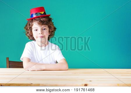 Little Curly Boy In A White Shirt And A Crimson Hat Clown Sitting At The Table Looking At The Camera