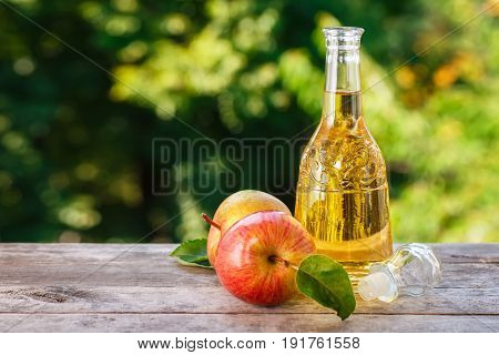 apple cider vinegar in glass decanter and ripe fresh apples on wooden table with blurred natural background