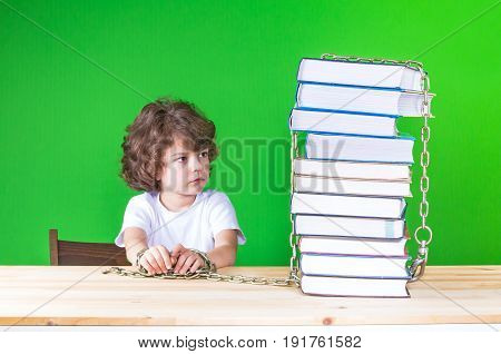 Sad Little Curly-headed Boy In A White Shirt Sits At A Table Chained To Books And Looks At Them. Clo