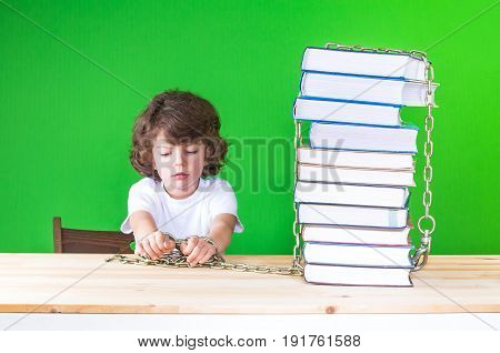 Sad Little Curly-headed Boy In A White T-shirt Sitting At His Desk And Looks At His Hands, Chained T