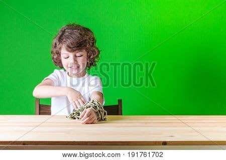 Little Curly Boy In A White Shirt Sits At A Table, Hands-free, Connected Chain. Close-up. Green Back