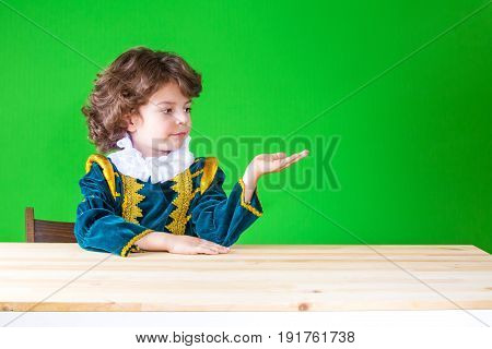 Cute Little Prince Sitting At A Table Holding In His Left Hand An Imaginary Thing, Looking At Him. C