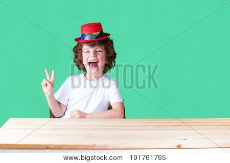 Little curly boy in a white t-shirt and a crimson hat clown sitting at a table laughing showing gesture
