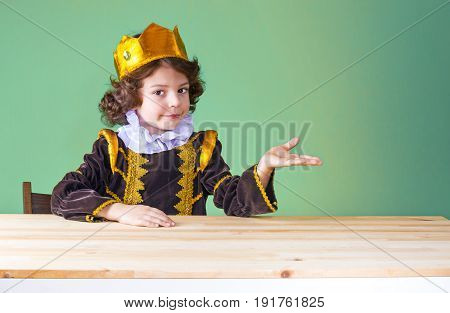 Little Cute King In The Crown Holds An Imaginary Object, Looking At The Camera. Close-up. Green Back