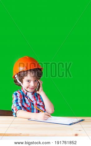 Serious little foreman with a phone in his hand smiling and looking at the camera. Close-up. Green background.