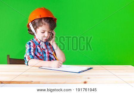 Young Cute Superintendent In A Helmet Speaks On The Phone, Sticking Out His Lip Pencil Writing In A