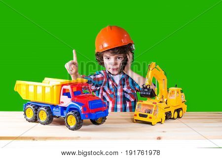Little Curly Foreman Indicates The Index Finger, Talking On The Phone Next To The Toy Construction E