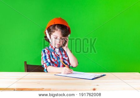 Young Handsome Foreman In Helmet Writing In Pencil In A Notebook. Close-up. Green Background.