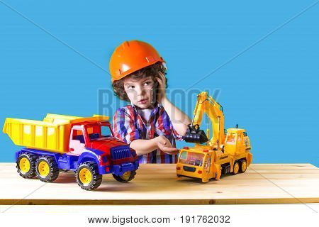 Little Curly Foreman Directs The Phone To Play With Trucks And Excavators. Close-up. Blue Background
