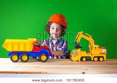 Little curly foreman in helmet construction equipment runs. Close-up. Green background.