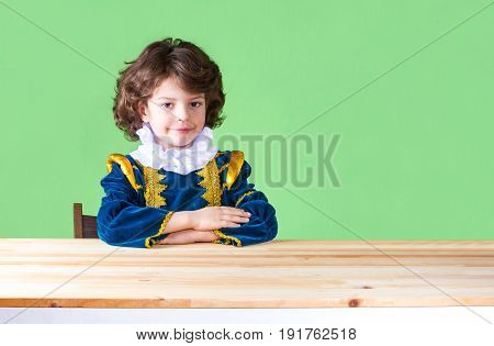 Young Pretty Kinky Prince Sitting At The Table Looking At The Camera. Close-up. Green Background.