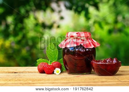 strawberry jam in jar and bowl, fresh berries on wooden table with green blurred natural background. Preserved fruits. Homemade jam in jar covered with paper. Still life with copy space