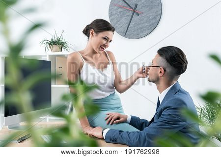Young Smiling Secretary Seducting Her Boss At Workplace In Office