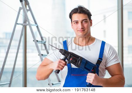 Young worker with hand drill