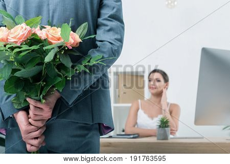 Businessman Holding Bouquet Of Roses For His Colleague Sitting At Workplace In Office