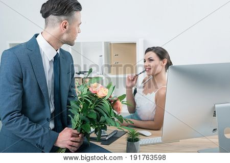 Businessman Presenting Bouquet Of Roses To His Colleague At Workplace In Office