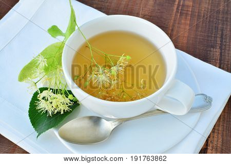 Cup of linden tea over white napkin on wooden table