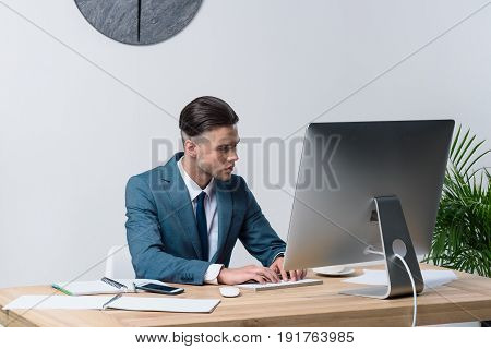 Focused Young Businessman Using Desktop Computer In Office