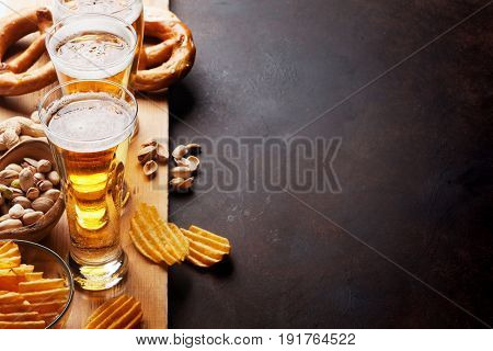Lager beer and snacks on stone table. Nuts, chips, pretzel. With copy space