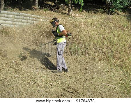 Alora Spain - June 5 2017: Council worker cutting dried shrub grass to prevent accidental fires