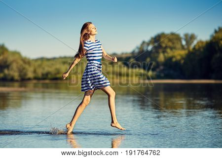 Beautiful Young Woman In Sailor Striped Dress Jamping On River Bank